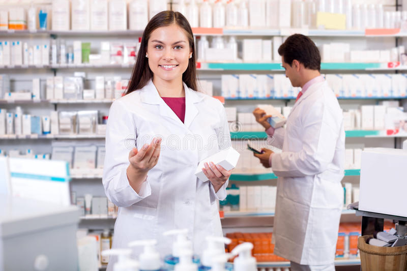 Portrait of two friendly pharmacists working. Portrait of two smiling friendly pharmacists working in modern farmacy royalty free stock images