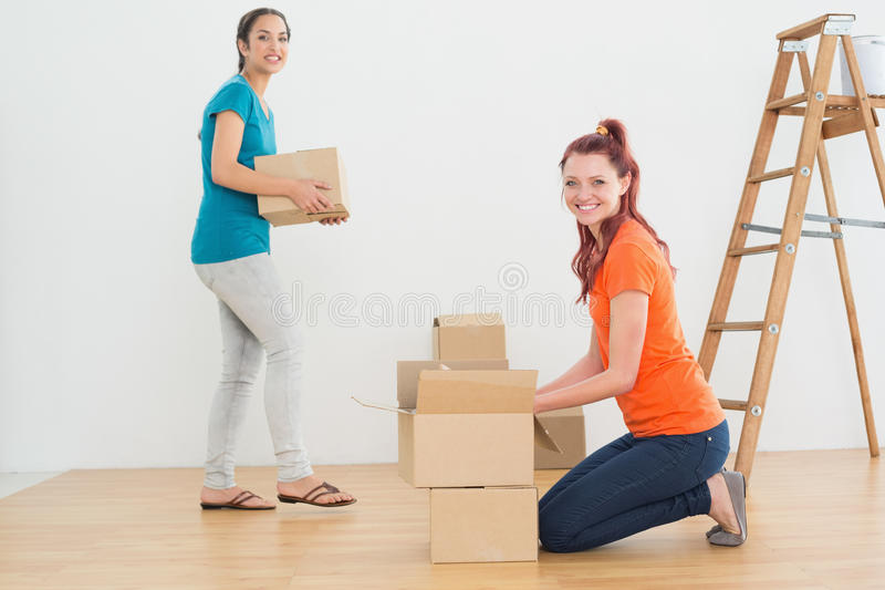 Portrait of two friends moving together in a new house stock photos