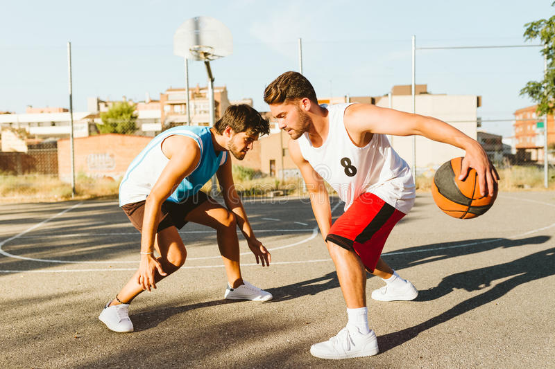 Portrait of two friends playing basketball on court. Outdoor portrait of two friends playing basketball on court royalty free stock photos
