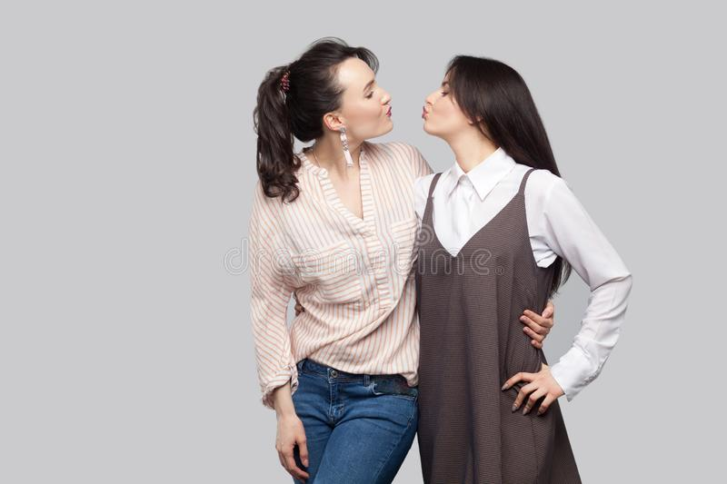 Portrait of two funny cheerful beautiful brunette best friends in casual style standing, hugging and looking at each other and stock photos