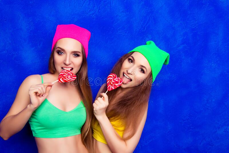 Portrait of two funny girls in color hats biting lollipops royalty free stock photo