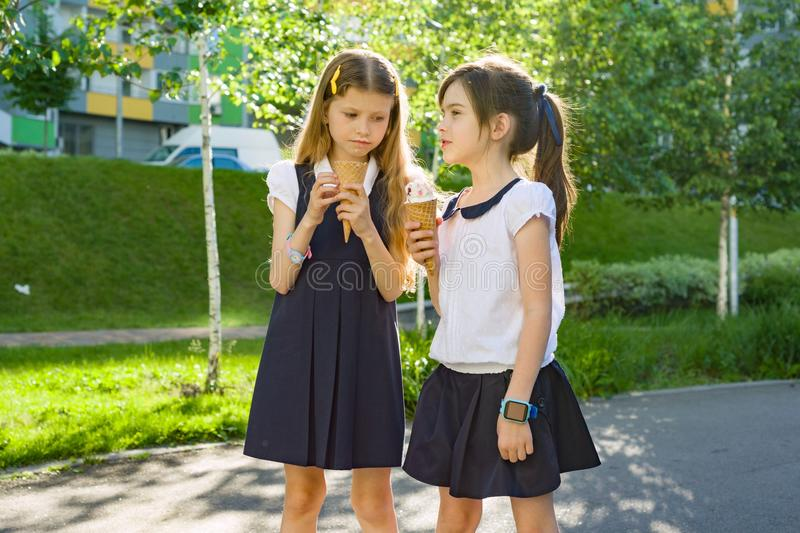Portrait of two girlfriends schoolgirls 7 years old in school uniform eating ice cream. Background city, summer, sidewalk, decorative bushes stock photography