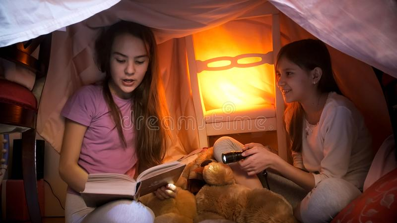 Portrait of two girls reading fairy tales in tent made of blankets at home royalty free stock photos
