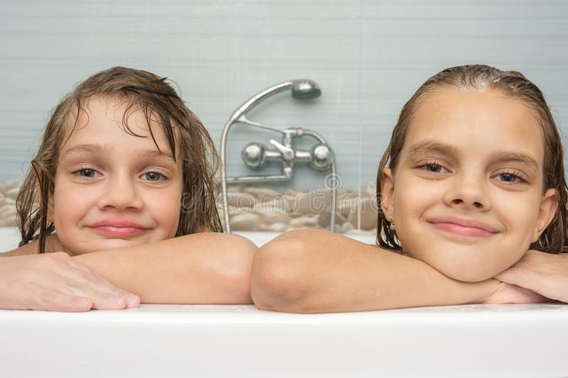 Portrait of two girls taking a bath stock photography