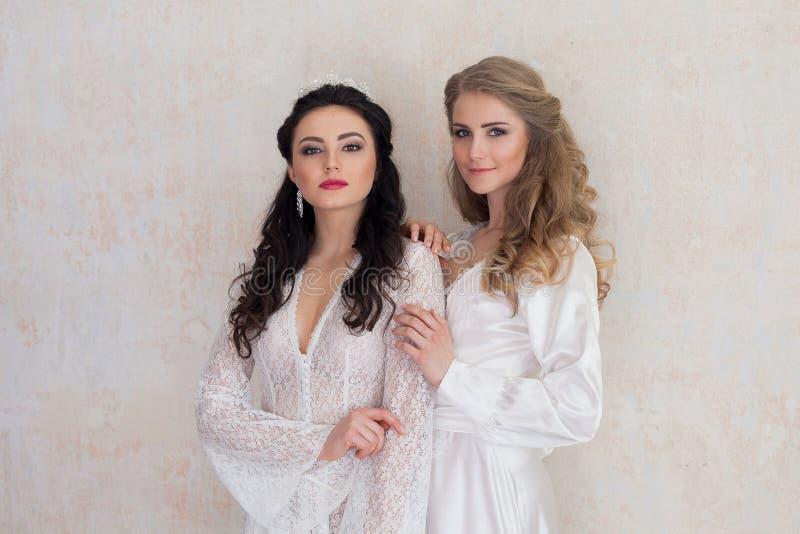 Portrait of two girls in white dresses wedding. Portrait of two girls in white dresses blonde and bojunetka wedding royalty free stock photography