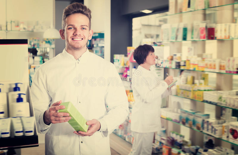 Portrait of two glad pharmacists. Working in modern farmacy royalty free stock photos
