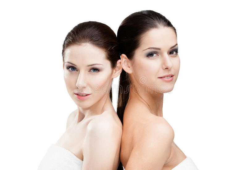 Portrait of two half naked women. Half length portrait of two half naked women who are ready for beauty procedures, isolated on white royalty free stock images