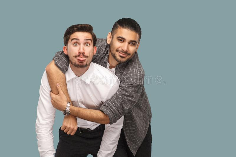 portrait of two handsome happy bearded friends standing, enjoying, hugging and looking at camera with smile and funny face and to royalty free stock images