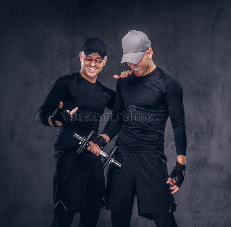 Portrait of two handsome young male dressed in a black sportswea royalty free stock images