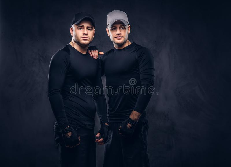 Portrait of two handsome young male dressed in a black sportswea royalty free stock image