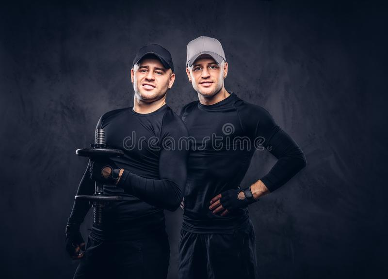 Portrait of two handsome young male dressed in a black sportswea stock images