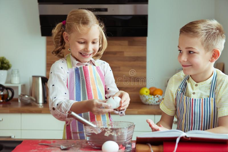 Portrait of two happy children which having fun during cooking c. Hristmas cookies at modern kitchen stock images