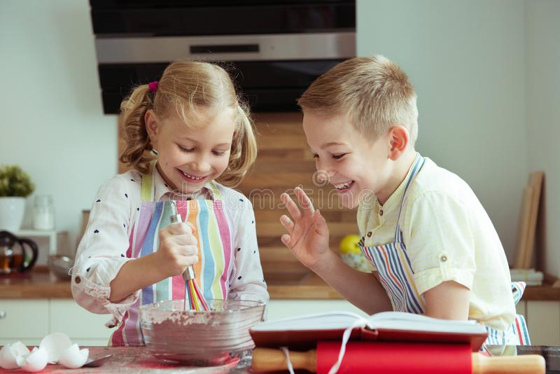 Portrait of two happy children which having fun during cooking c. Hristmas cookies at modern kitchen royalty free stock photos
