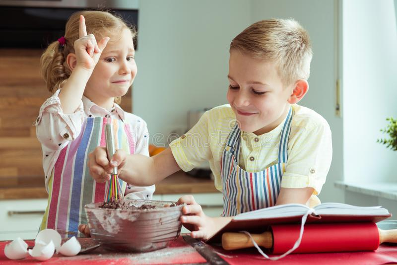 Portrait of two happy children which having fun during cooking c. Hristmas cookies at modern kitchen royalty free stock image