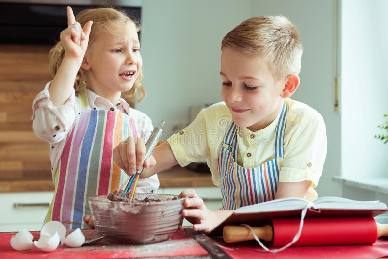 Portrait of two happy children which having fun during cooking c. Hristmas cookies at modern kitchen stock photography