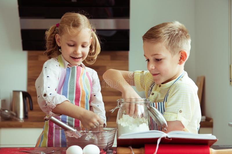 Portrait of two happy children which having fun during cooking c. Hristmas cookies at modern kitchen stock photo
