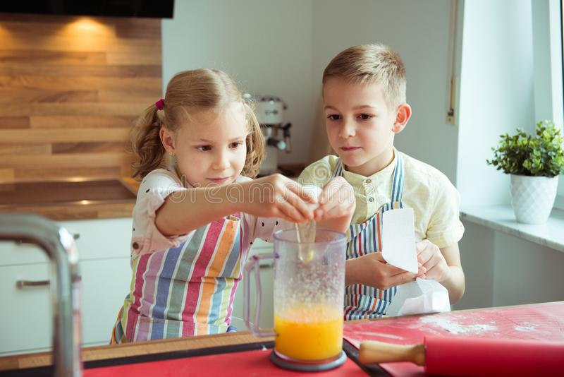Portrait of two happy children which having fun during cooking c. Hristmas cookies at modern kitchen royalty free stock images
