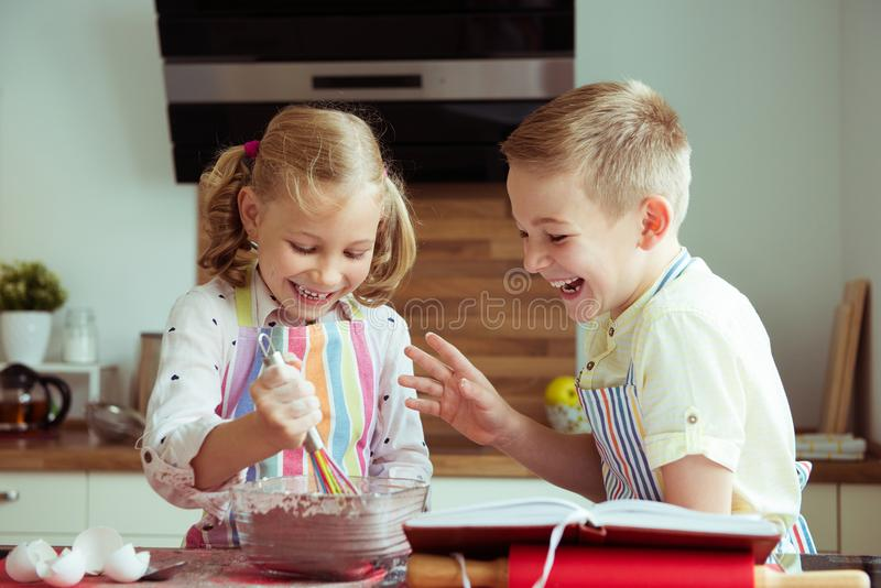 Portrait of two happy children which having fun during cooking c. Hristmas cookies at modern kitchen stock image