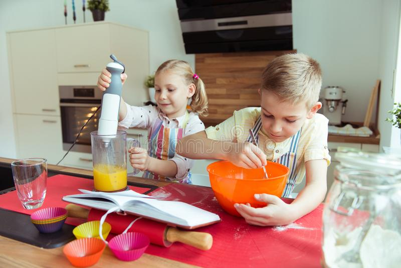 Portrait of two happy and cute little children which having fun. During preparing muffins with blender in modern kitchen stock image