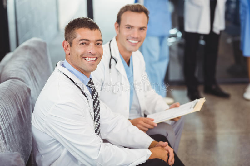 Portrait of two happy doctors with clipboard stock photo