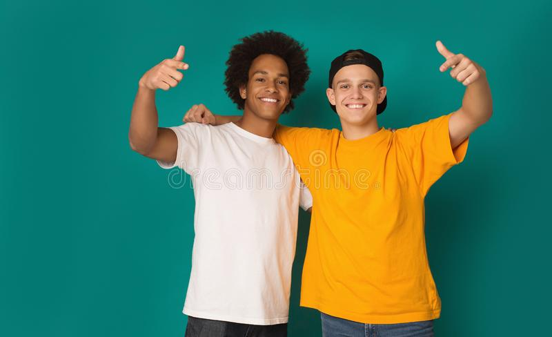 Portrait of two happy friends pointing fingers at camera stock images
