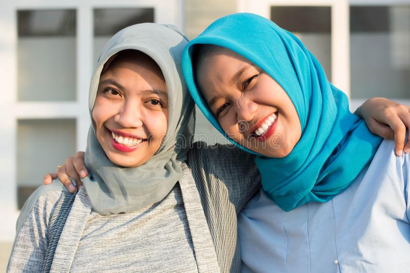 Portrait of two happy hijab women, smiling at the camera while embracing in front of their house stock photography
