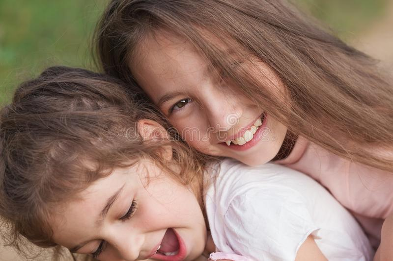 Portrait of Two Happy little girls laughing and hugging at the summer park. Happy childhood concept royalty free stock images