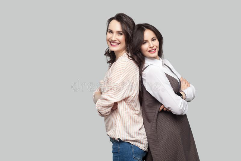 Portrait of two happy satisfied beautiful partners in casual style standing back to back with crossed arms and looking at camera stock images