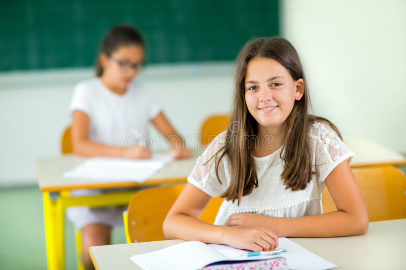 Portrait of two happy schoolgirls in a classroom stock photography