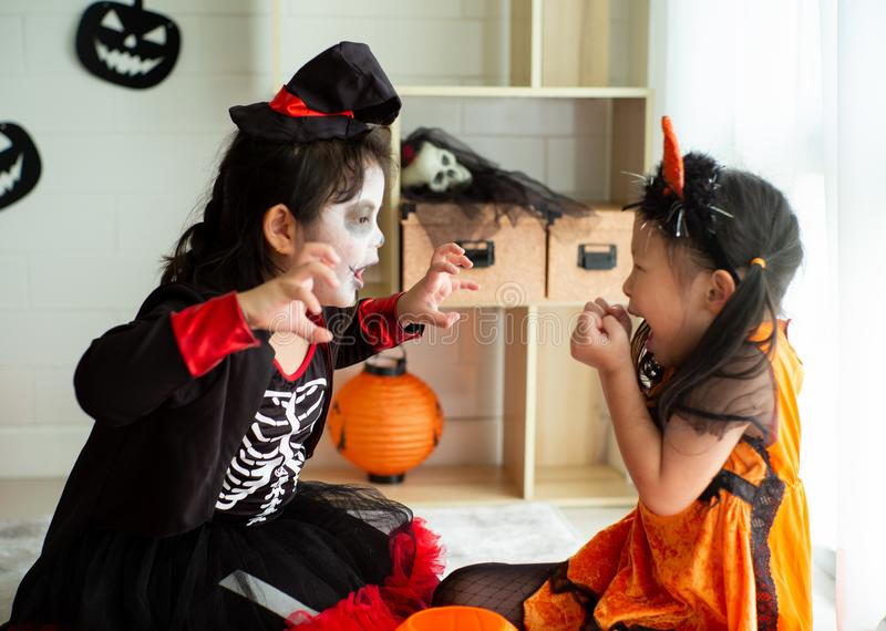 Portrait of two happy sisters in the Halloween costume. Sharing the candy and chocolate from trick or treat royalty free stock photo