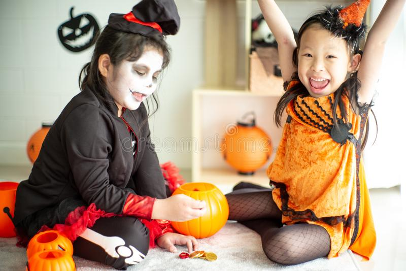 Portrait of two happy sisters in the Halloween costume. Sharing the candy and chocolate from trick or treat stock photos