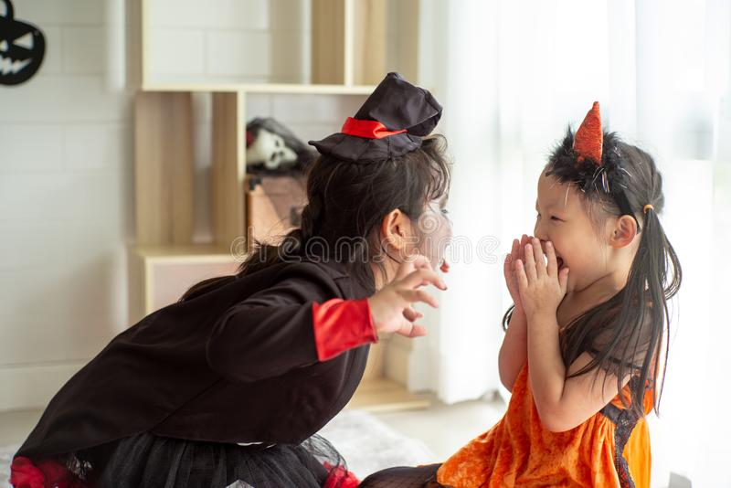 Portrait of two happy sisters in the Halloween costume sharing t. He candy and chocolate from trick or treat royalty free stock image