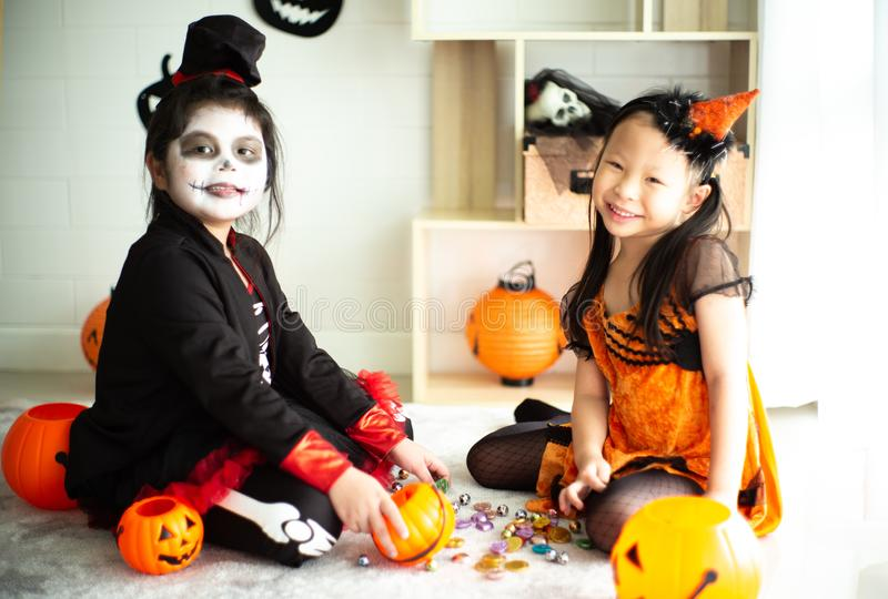 Portrait of two happy sisters in the Halloween costume sharing t. He candy and chocolate from trick or treat stock images