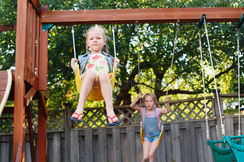 Two happy smiling little girls on swing on backyard playground outside on summer day royalty free stock photos