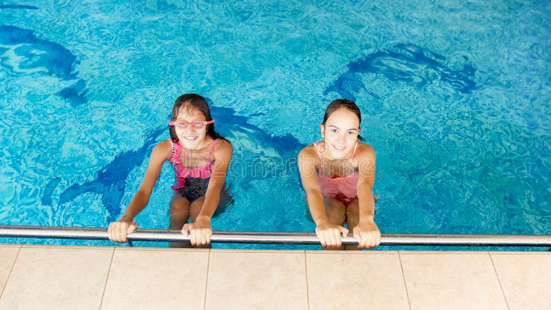 Portrait of two happy smiling teenage girls in the indoors swimming pool royalty free stock photography