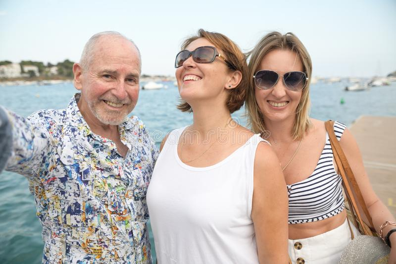 Portrait of two happy women and an older man over seaside promenade taking selfie stock images