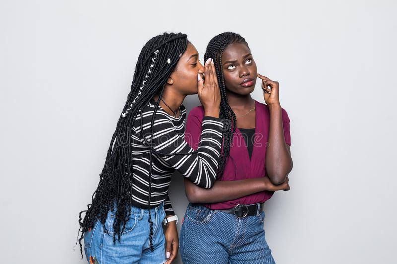 Portrait of two happy young african women sharing secrets isolated over white background. Portrait of two happy young african women sharing secrets isolated stock photos