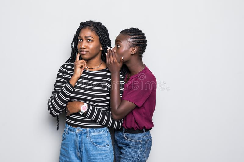 Portrait of two happy young african women sharing secrets isolated over white background. Portrait of two happy young african women sharing secrets isolated stock photo