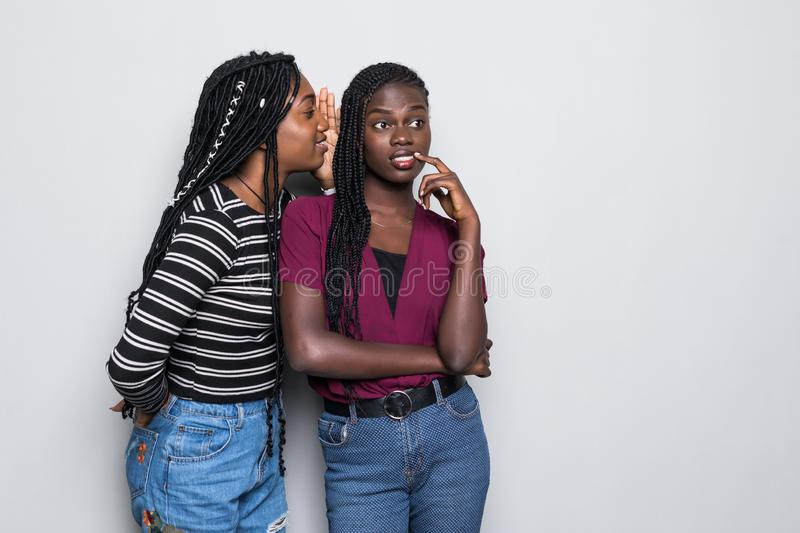 Portrait of two happy young african women sharing secrets isolated over white background. Portrait of two happy young african women sharing secrets over white stock photos