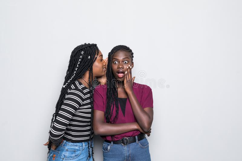 Portrait of two happy young african women sharing secrets isolated over white background. Portrait of two happy young african women sharing secrets over white royalty free stock photos