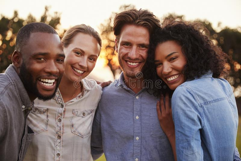 Portrait of two happy young couples smiling and embracing stock photos
