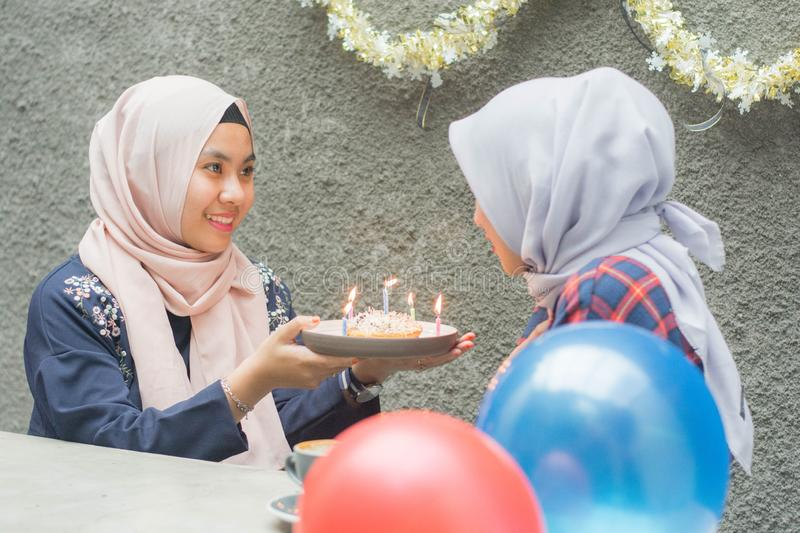 Portrait of two hijab woman bestfriend having time together in celebrate event. Portrait of two hijab women bestfriend celebrate birthday with pancake and and royalty free stock image