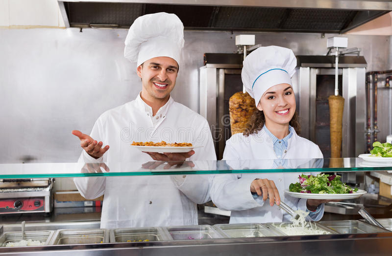 Portrait of two hospitable chefs with kebab at fastfood place royalty free stock images