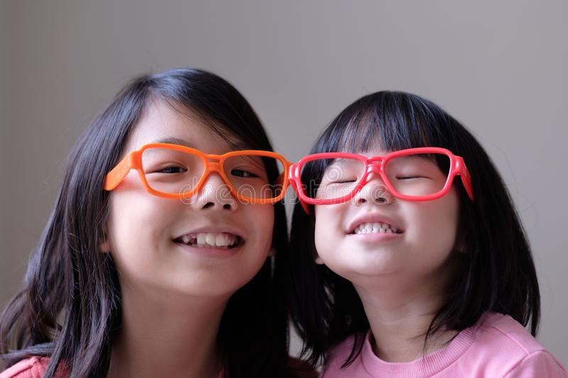 Two little sisters with big eyeglasses stock images