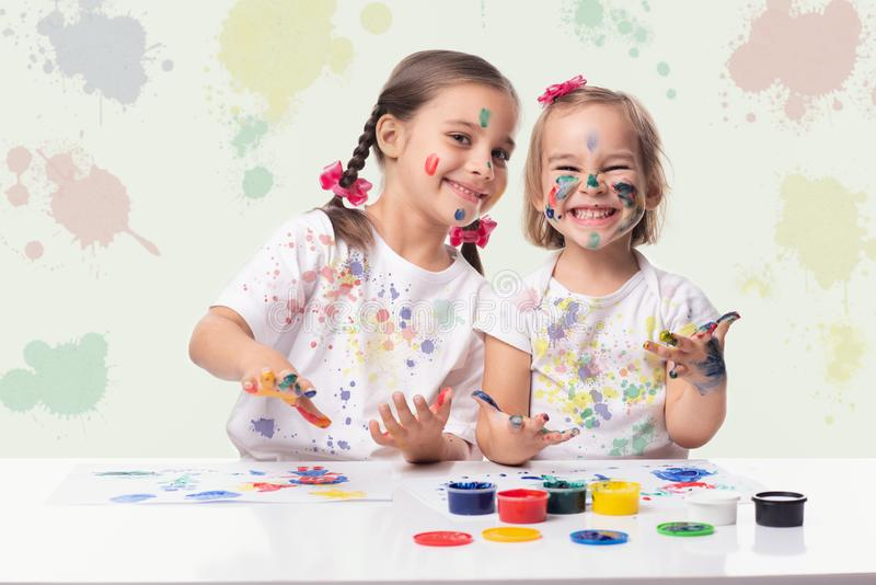 Portrait of Two Little Child Girls Playing with Finger Paint stock image