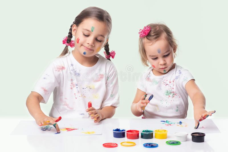 Portrait of Two Little Child Girls Playing with Finger Paint royalty free stock images