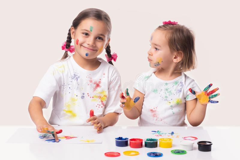 Portrait of Two Little Child Girls Playing with Finger Paint stock images
