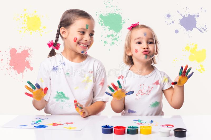 Portrait of Two Little Child Girls Playing with Finger Paint royalty free stock photo