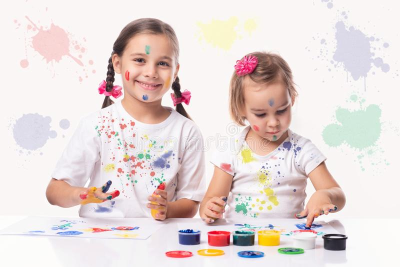 Portrait of Two Little Child Girls Playing with Finger Paint royalty free stock image