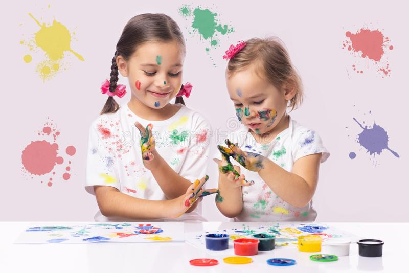 Portrait of Two Little Child Girls Playing with Finger Paint stock photography